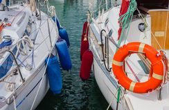 Two boats anchored at the  harbor. Detail of two boats anchored with the typical colored fenders and the characteristic orange life-buoy Royalty Free Stock Photo