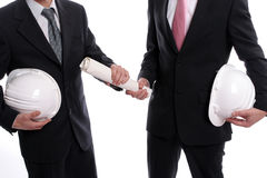 Detail of two business man with safety hats. Exchanging a new project, isolated in white background royalty free stock photo