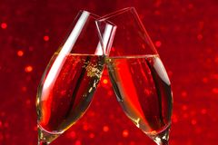 Detail of two champagne flutes on red light bokeh background. Detail of two champagne flutes make cheers on red light bokeh background stock photos