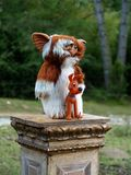 Detail of a gremlin and a Pluto dog. Detail of two dolls of a gremlin and a Pluto dog on a plaster pedestal in a meadow of the Navarrese mountain Stock Image