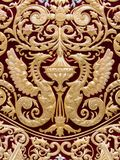 Detail of mantle, Virgin of Regla, Holy Week in Seville. Detail of two dragons embroidered in gold on red velvet in the mantle of the Virgin of Regla, Holy Week royalty free stock photo