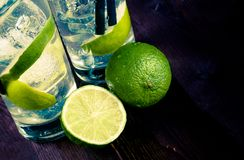 Detail of two glasses with cocktail and ice with lime slice on old wood background Royalty Free Stock Image