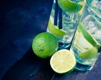 Detail of two glasses with cocktail and ice with lime slice on old wood background Royalty Free Stock Photos