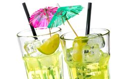 Detail of two glasses with cocktail and ice with lime slice on white background Stock Photo
