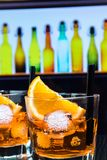 Detail of two glasses of spritz aperitif aperol cocktail with orange slices and ice cubes on bar table, disco atmosphere backgroun Stock Photos