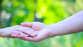 Detail of two lovers joining hands. Blur background stock video footage