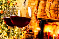 Detail of two red wine glasses against christmas tree background Royalty Free Stock Photography