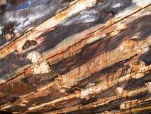 Detail und Nahaufnahme des alten und farbigen hölzernen Rumpfs des Bootes, alte Malerei mit Sprüngen und hölzerne Beschaffenheit Stockbild