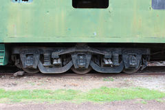 Detail of the undercarriage of a vintage rusted green train car. Horizontal aspect Stock Photo