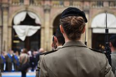 Detail with uniformed women standing during the military ceremony in Bologna. Italy. In the foreground, a woman seen from behind with a bayonet rifle royalty free stock photos