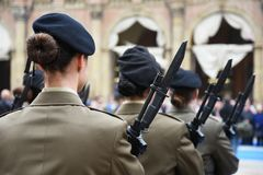 Detail with uniformed women standing during the military ceremony in Bologna. Italy. In the foreground, a woman seen from behind with a bayonet rifle royalty free stock images