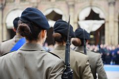Detail with uniformed women standing during the military ceremony in Bologna. Italy. In the foreground, a woman seen from behind with a bayonet rifle royalty free stock image