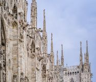 Detail of upper section of the Duomo di Milano populated with statuary and spires. The Duomo di Milano has more statues attached to the building than any other Royalty Free Stock Photos