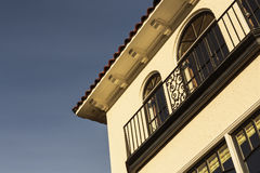 Detail of upscale home with balcony. Detail of upscale home, showing balconies, arched windows, roof edge, and cornice. House sits against blue sky Stock Photos
