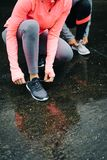 Women ready for running and training under the rain. Detail of urban athletes lacing sport footwear for running over asphalt under the rain. Two women getting Royalty Free Stock Photo