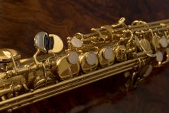 Detail valves saxophone close up. Detail valves golden saxophone on a wooden background Stock Photos