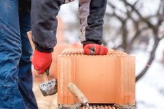 Detail van arbeider, de ingenieur van de metselaarsbouw het bevestigen bakstenen en de bouwmuren bij nieuw huis op een de winterd Stock Afbeeldingen