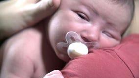 Detail van baby met fopspeen in zijn mond stock footage