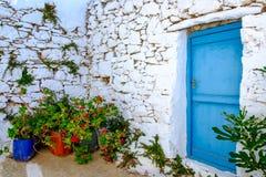 Detail van blauwe deur, witte steenmuur en kleurrijke bloemen stock afbeeldingen