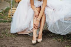 Detail van bruids benen met schoenen die op de houten lijst zitten stock foto's
