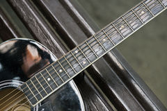 Detail van bruine die gitaar op parkbank wordt geplaatst Stock Afbeeldingen