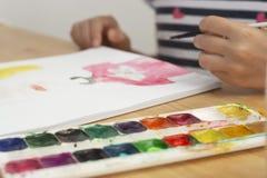 Detail van de hand van het kind het schilderen met waterverf, hobby, onderwijs stock foto
