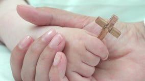 Detail van de hand van de de holdingsbaby van de moederhand met christelijk dwars, vroeg onderwijs, reële waarden om het nieuw le stock video