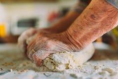 Detail van de handen die van de gerimpelde oude vrouw deegwaren voorbereiden stock afbeelding