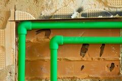 Detail van een nieuw hydraulisch systeem met een groene polypropyleenpijpen voor heet en koud water in een Italiaanse bouwwerf stock afbeeldingen