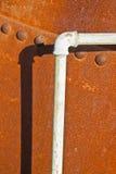 Detail van een pijpleiding tegen een roestige vastgenagelde metaaltank Royalty-vrije Stock Foto