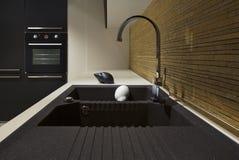 Detail van een zwart modern keuken en een hout Stock Foto