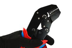 Detail van eind plooiende persbuigtang met gesloten die kaken, in linkerhand in dun zwart nylon wordt het gehouden/de polyester/s stock afbeeldingen