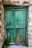 Detail van groene houten deur in uitstekende steenmuur stock foto's