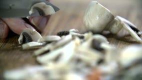 Detail van groot keukenmes die kleine knooppaddestoel snijden stock footage