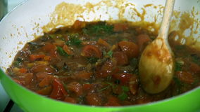 Detail van het bewegen van de groenten in de pan met een gietlepel in langzame motie stock videobeelden