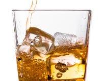 Detail van het gieten van Schotse whisky in glas met ijsblokjes op wit Stock Afbeelding