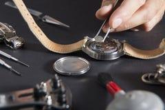 Detail van het werk van een horlogemaker die een batterij vervangt stock afbeelding