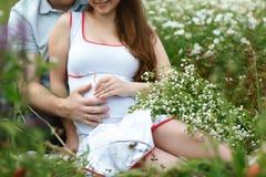 Detail van jong zwanger paar op de bloemen van de gebieds witte kamille Sluit omhoog Wachtende baby stock foto's