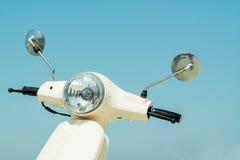Detail van klassieke autoped met koplamp en stuur tegen sk Stock Foto's