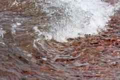 Detail van Kleine brekende die golf bij het strand van Aqaba in Jordanië, met ruw grint wordt behandeld royalty-vrije stock afbeeldingen