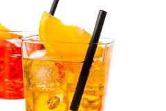 Detail van rode en gele cocktail met oranje die plak op bovenkant en stro op witte achtergrond wordt geïsoleerd Stock Afbeelding