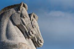 Detail van twee marmeren paardhoofden tegen blauwe hemel stock foto