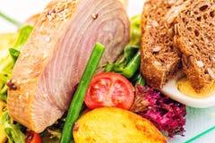 Detail van verse groentesalade met tomaten, aardappels, eieren, slabonen en geroosterd tonijnlapje vlees op glasplaat op wit Stock Foto's