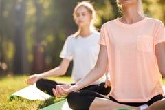 Detail van vrouwen die yoga doen in openlucht bij zonsopgang Ochtendmeditatie stock foto's