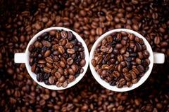 Detail van witte koppen van koffie die met koffiebonen worden gevuld Royalty-vrije Stock Fotografie