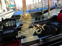 Detail of a Venetian Gondola. A horse-like shape little sculpture, detail of a gondola, in gold tones , Grand Channel, Venice, Italy Royalty Free Stock Images
