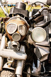 Detail of veteran motorbike with symbolic gas mask, retro photo. Detail of veteran motorbike with symbolic gas mask. Meeting bikers. Front view. Handlebars and stock photography