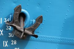 Black painted anchor on a blue boat stock photo