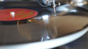 Detail view of black vinyl record spinning on old turntable. Needle sliding smoothly on vintage plate playing music. Retro concept. Slow motion stock footage