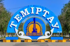 Detail View of the colorful Emblem and Flag of City Temirtau on the End of the main Promenade. Outgoing Street with many Threes to royalty free stock photography